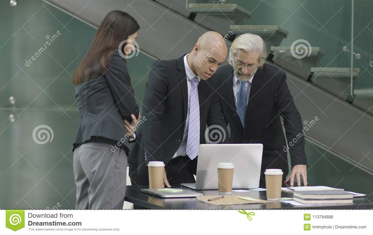 Three corporate executives meeting in modern office
