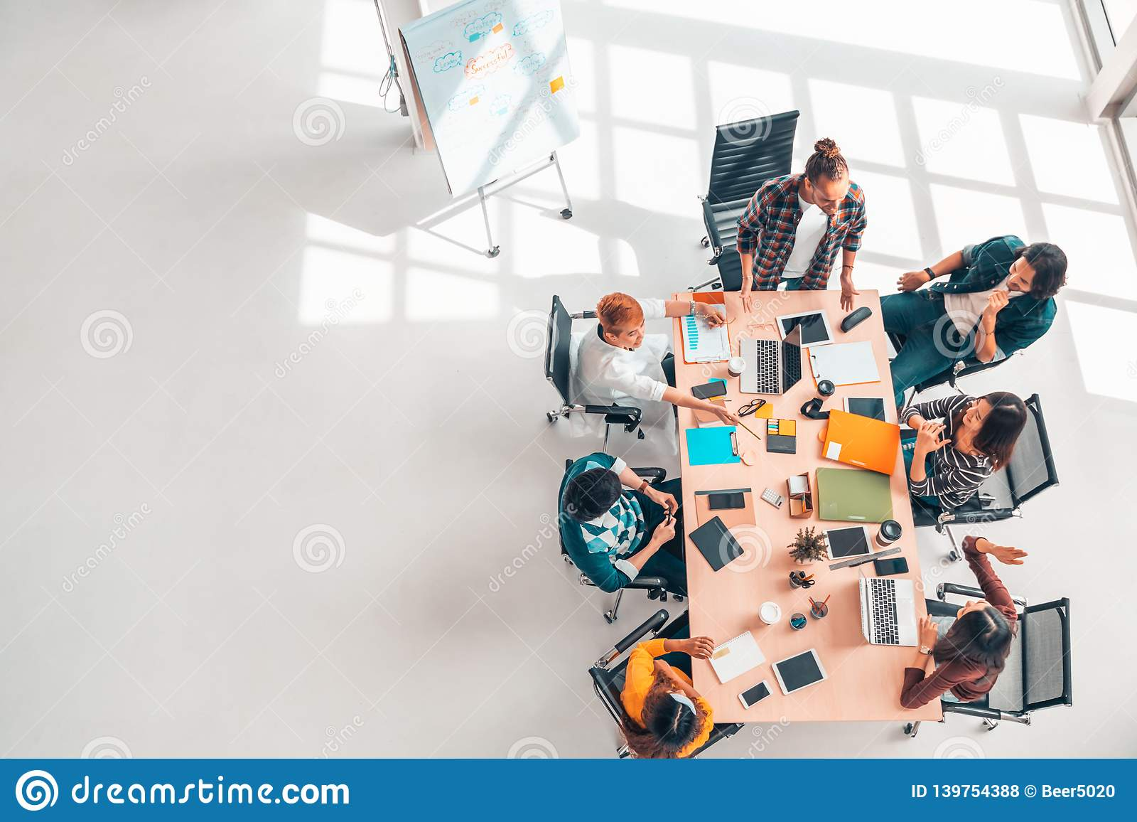 Multiethnic diverse group of business coworkers in team meeting discussion, top view modern office with copy space