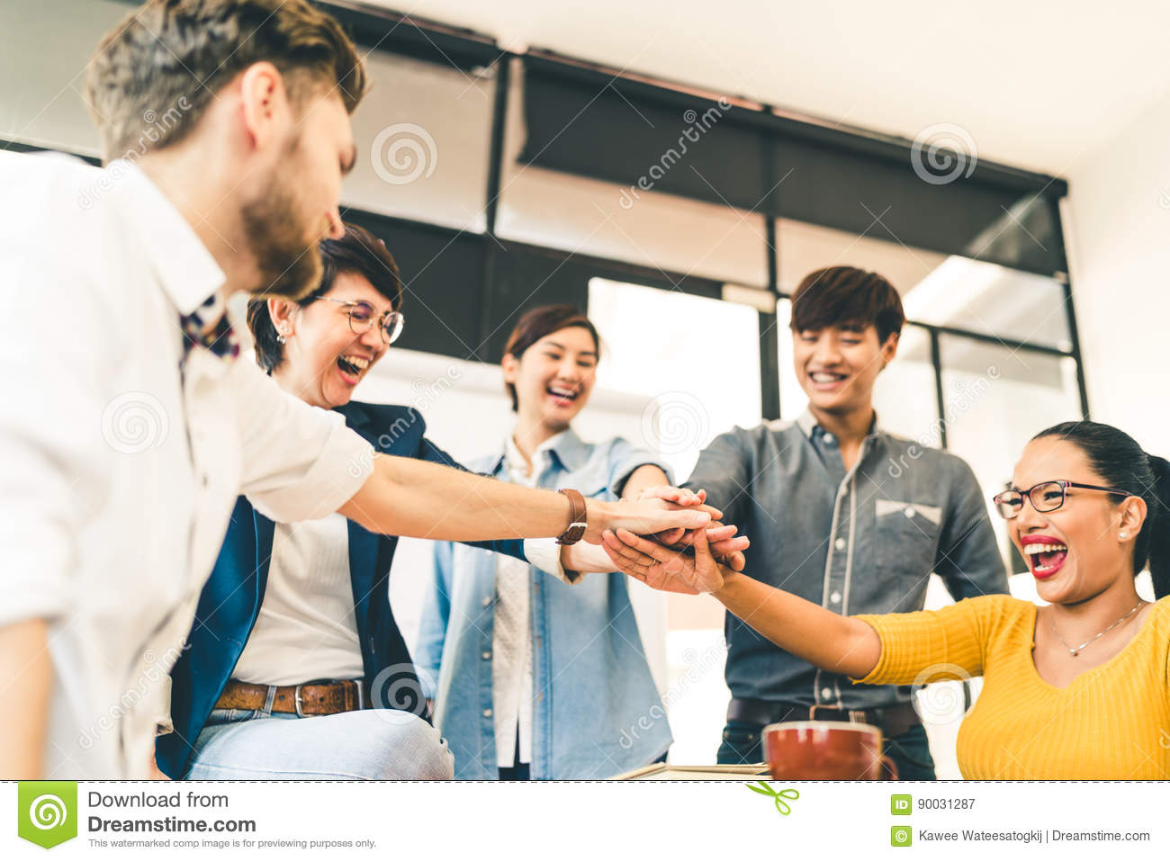Multiethnic diverse group of happy colleagues join hands together. Creative team, casual business coworker, or college students