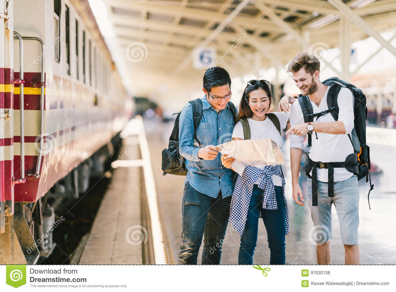 Multiethnic group of friends, backpack travelers, or college students using local map navigation together at train station