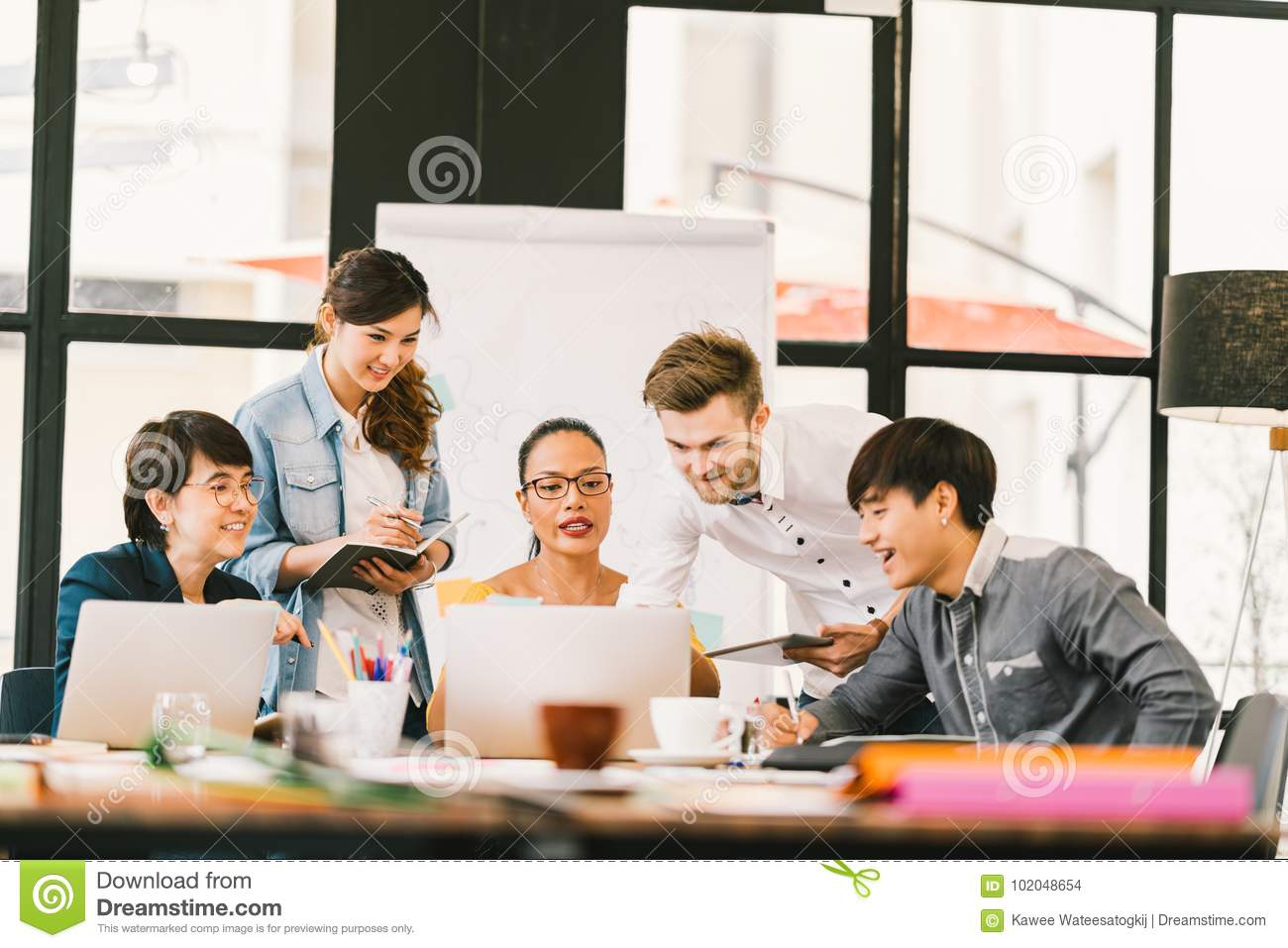 Multiethnic team discussion using laptop, digital tablet. Coworker partnership, college student meeting. Small business concept