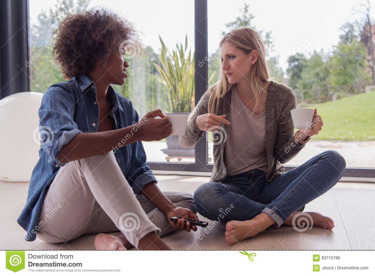 Multiethnic Women Sit On The Floor And Drinking Coffee Stock Photo