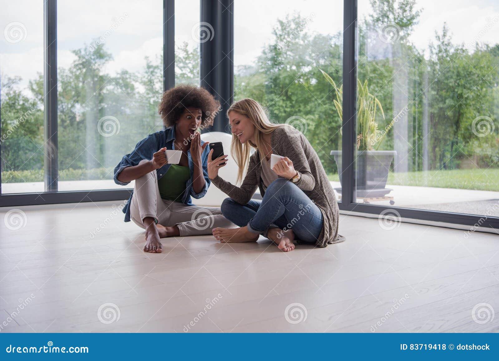 Multiethnic Women Sit On The Floor And Drinking Coffee Stock Photo