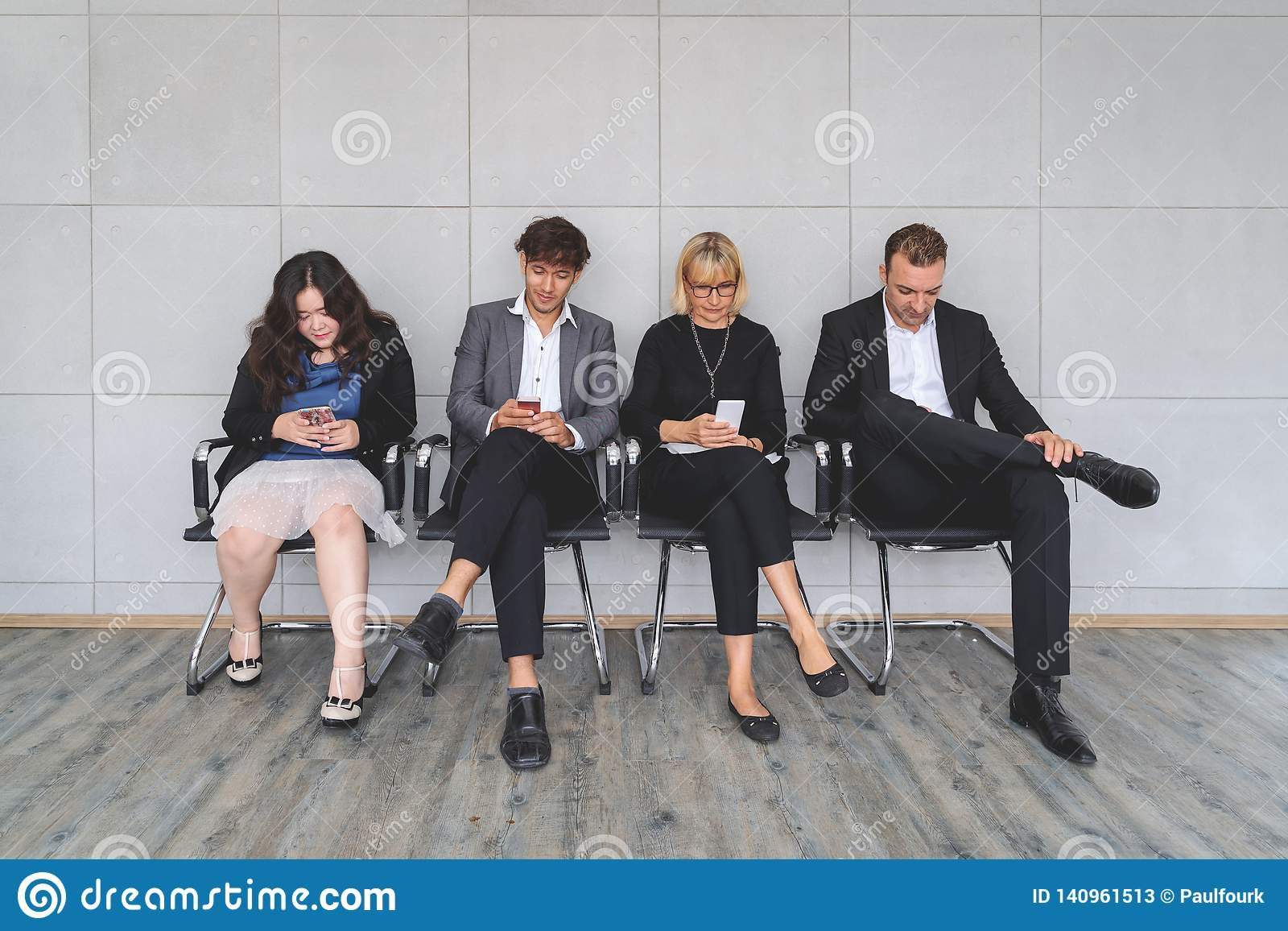 Multiethnic work applicants busy using laptops and smartphones preparing for recruiting talk, diverse job candidates sit in queue