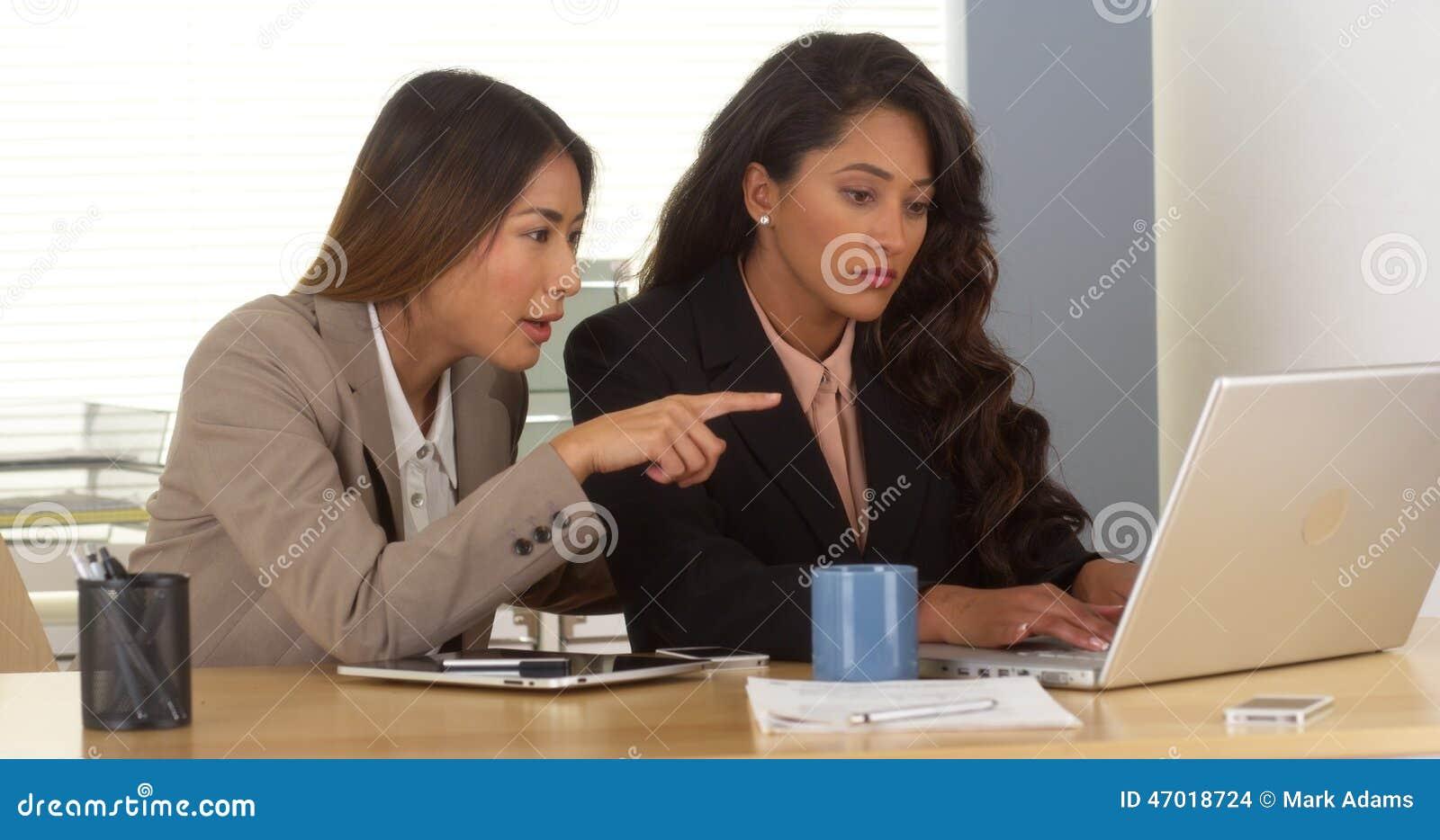 Multiethnische Geschäftsfrauen, die an Laptop arbeiten