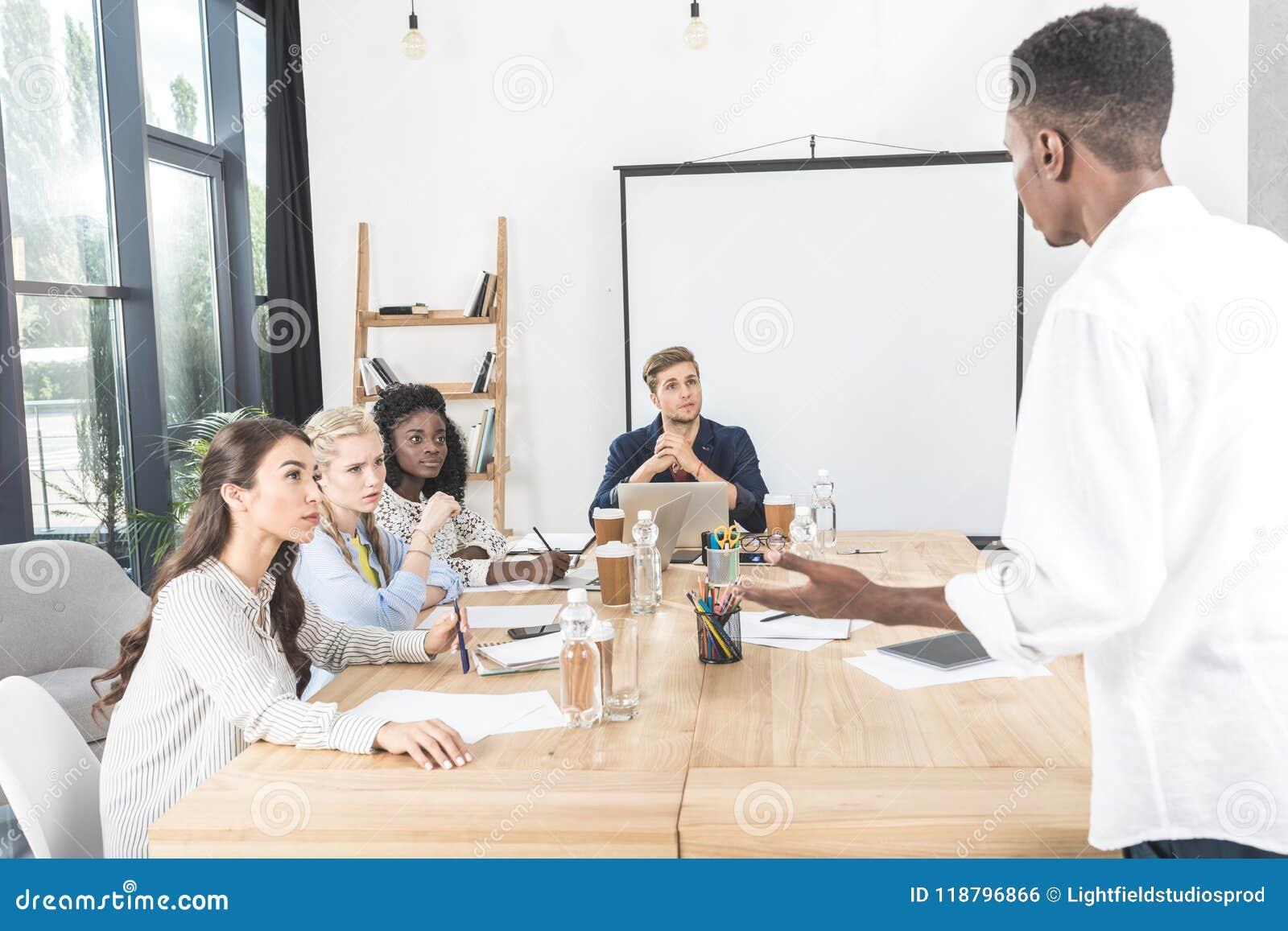 Multiethnische Gruppe fokussierte Kollegen, die auf Afrikaner hören