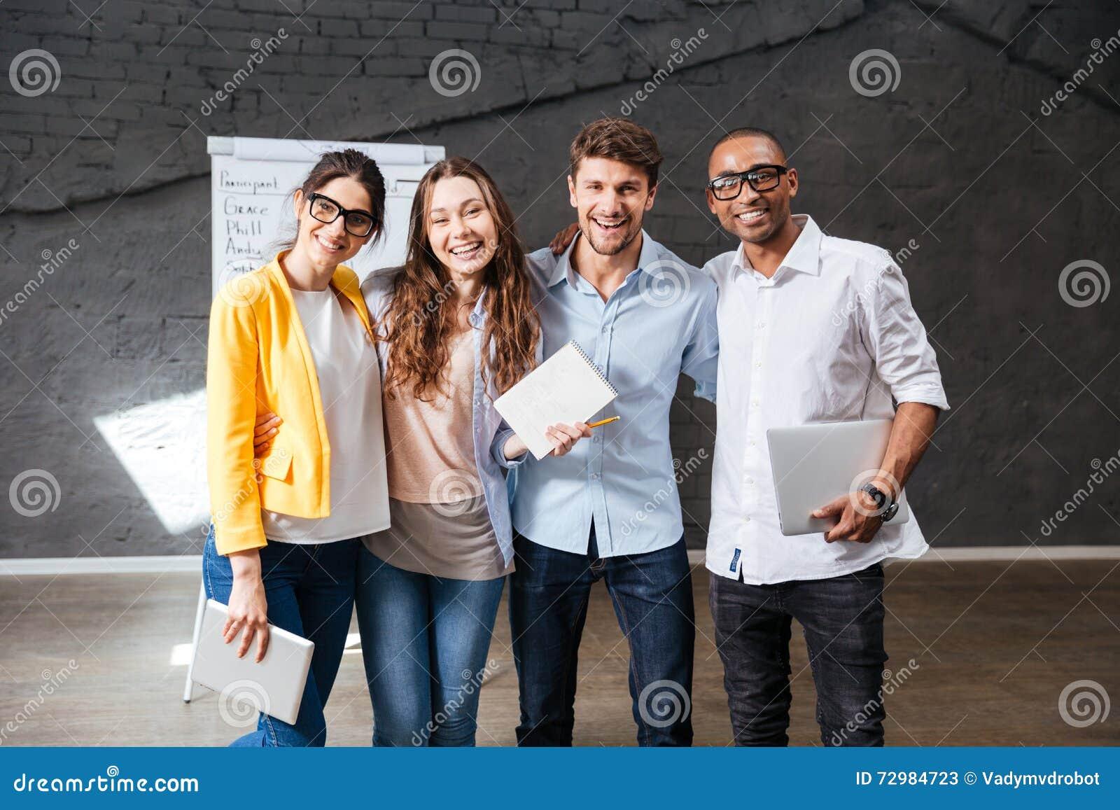 Multiethnische Gruppe glückliche junge Geschäftsleute, die im Büro stehen