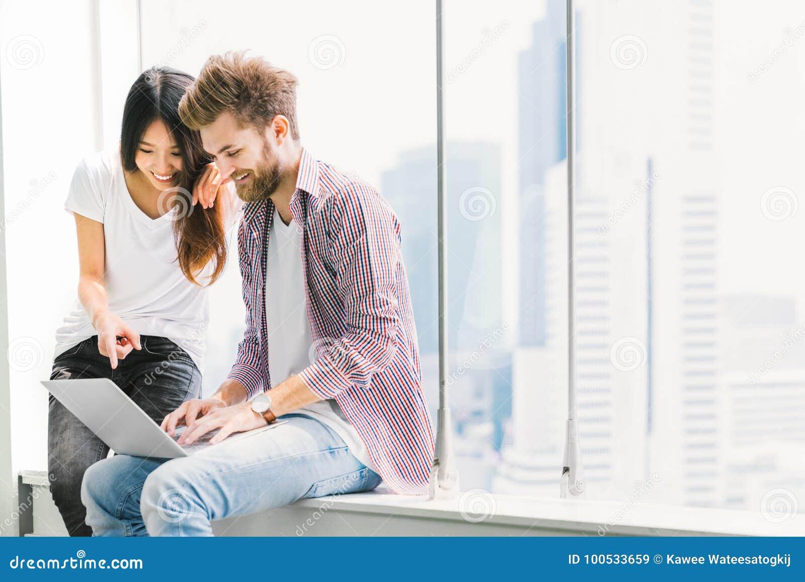 Multiethnische junge Paare oder Student, der zusammen Notizbuchlaptop im Campus oder im Büro verwendet Ein leuchtendes Mädchen, e