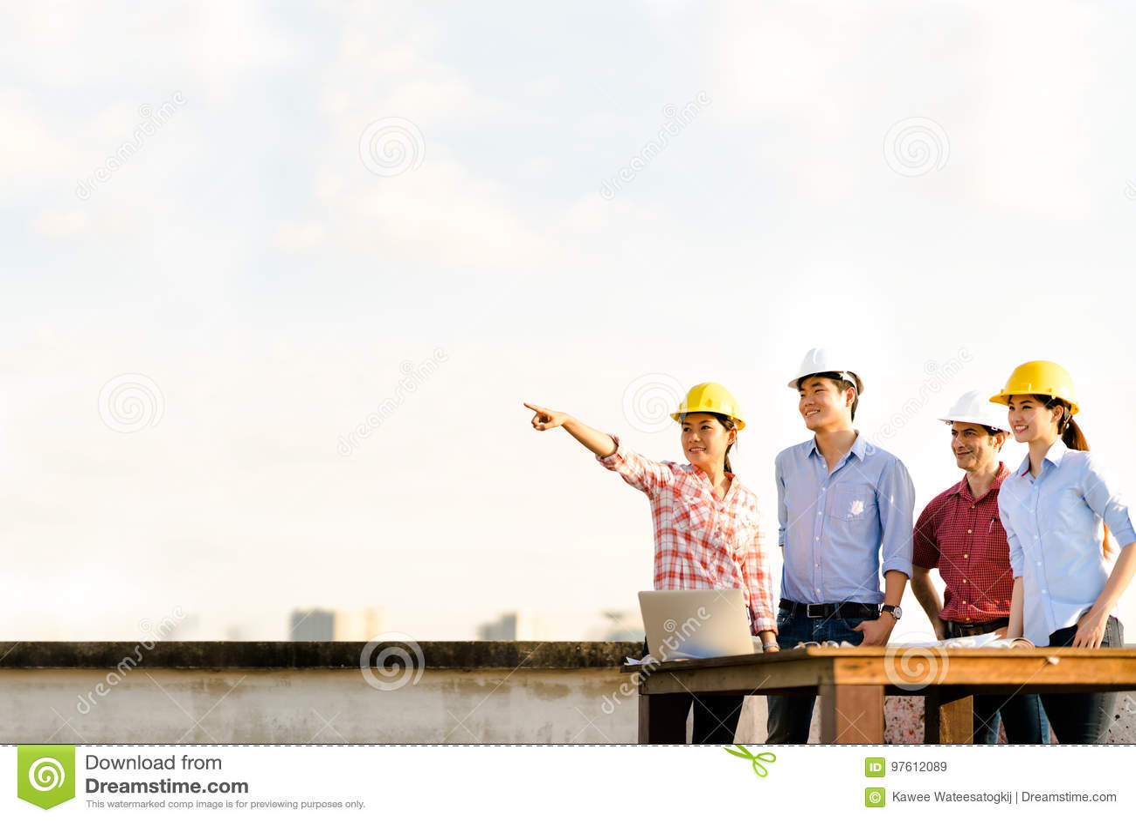 Multietnisk olik grupp av teknikerer eller affärspartners på konstruktionsplatsen som pekar in mot kopieringsutrymme på himmel un