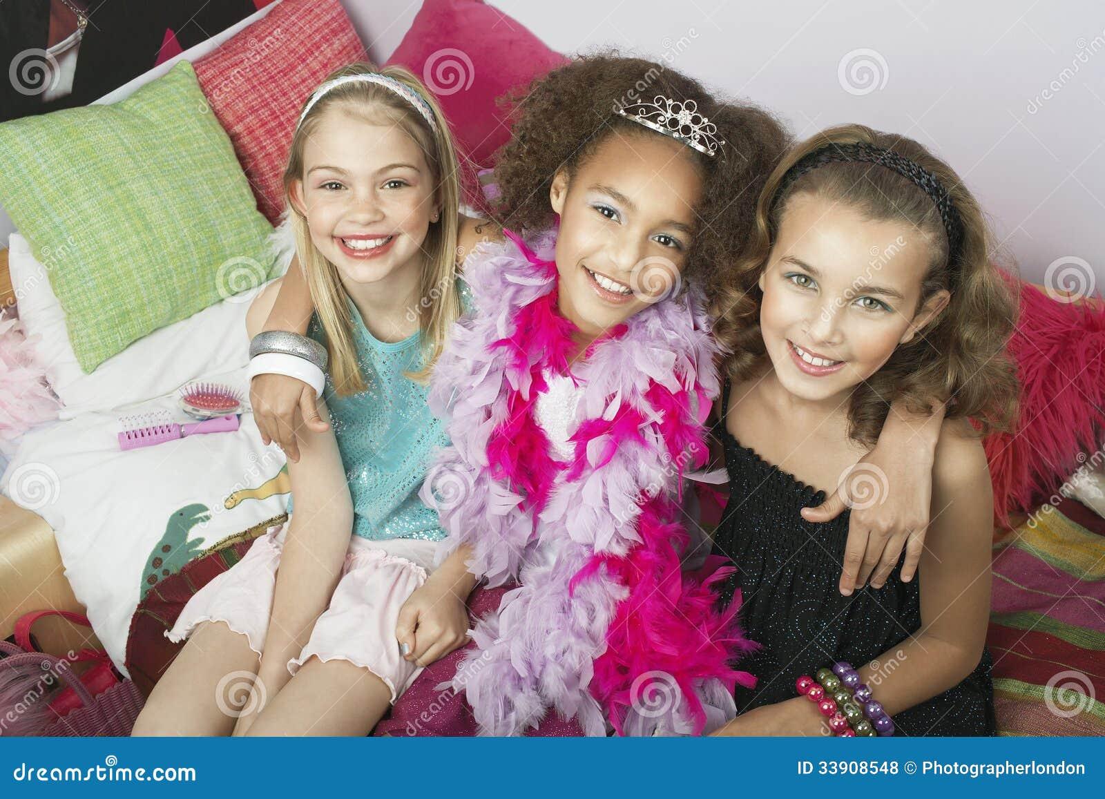 Multietniska flickor som sitter på moderiktiga Sofa At Slumber Party