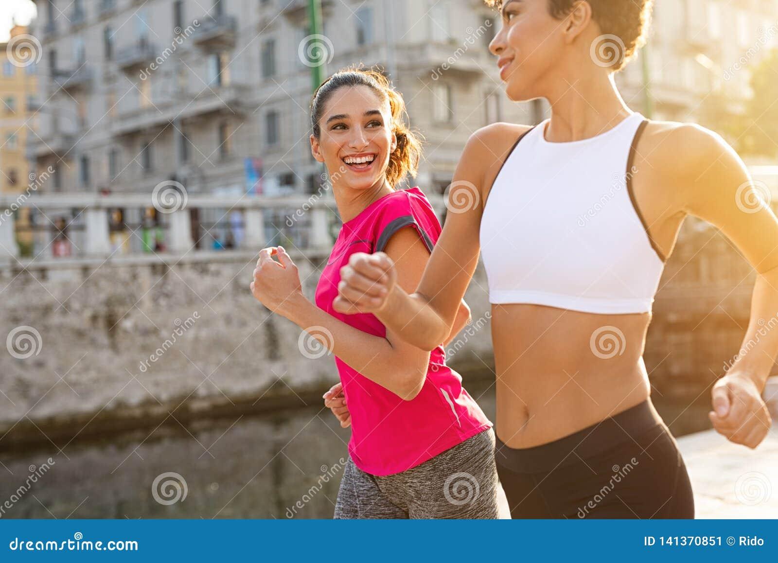 Multietniska kvinnor som joggar på gatan