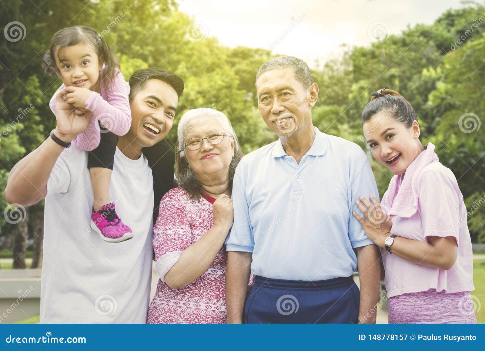 Multigeneratiefamilie die in het park glimlachen