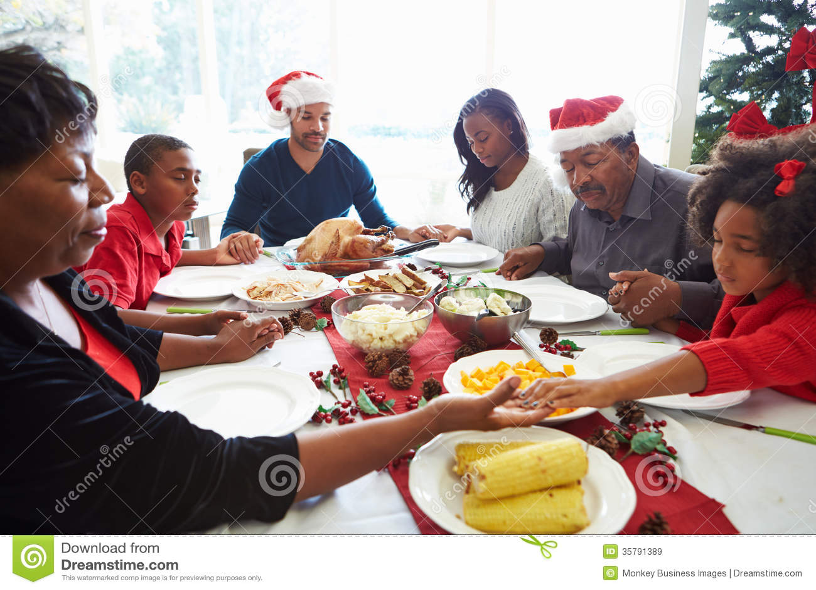 Multigeneratiefamilie die vóór Kerstmismaaltijd bidden
