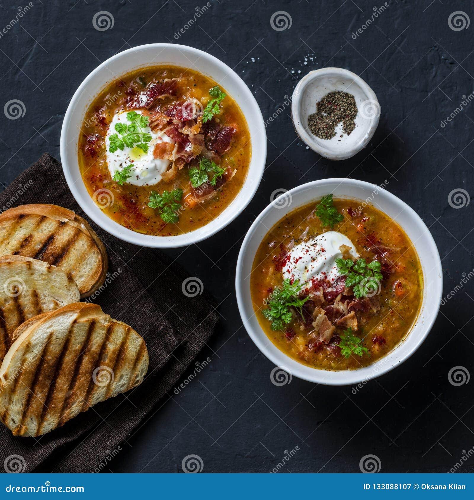 Multikorrel en groentesoep met geroosterde kaassandwiches en knapperig bacon op een donkere achtergrond, hoogste mening Heerlijk