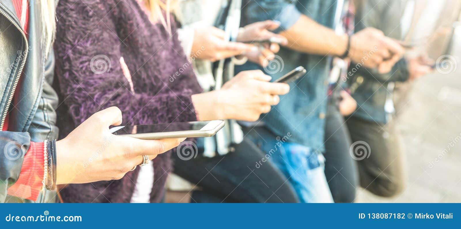 Multikulturelle Freundgruppe unter Verwendung des Smartphone am Universitätshinterhofbruch - Leutehände gewöhnt durch intelligent