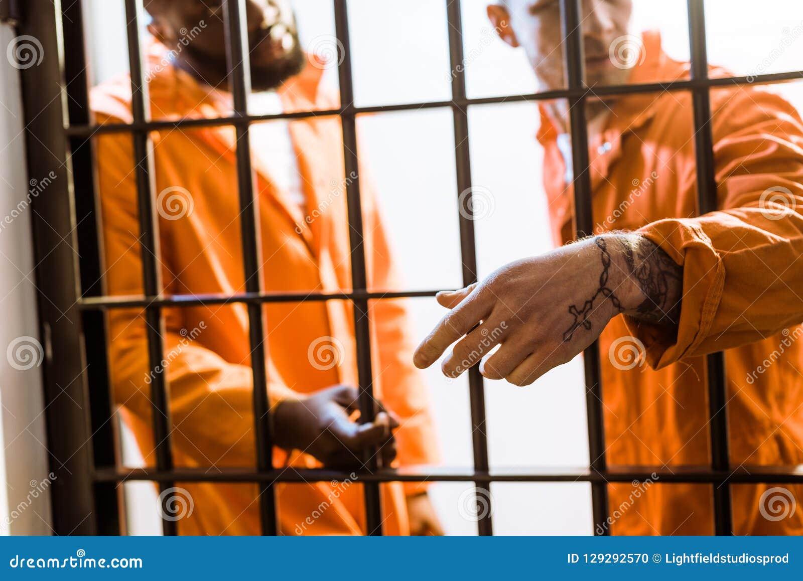 Multikulturelle Gefangene, die nahe Gefängnisstangen stehen
