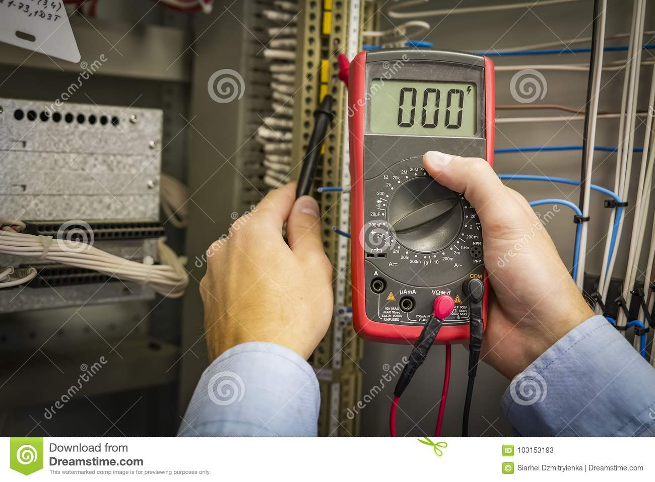 Multimeter In Hands Of Electrician Engineer Closeup On Electric Electrical Wiring Test Panel Background Circuit Service