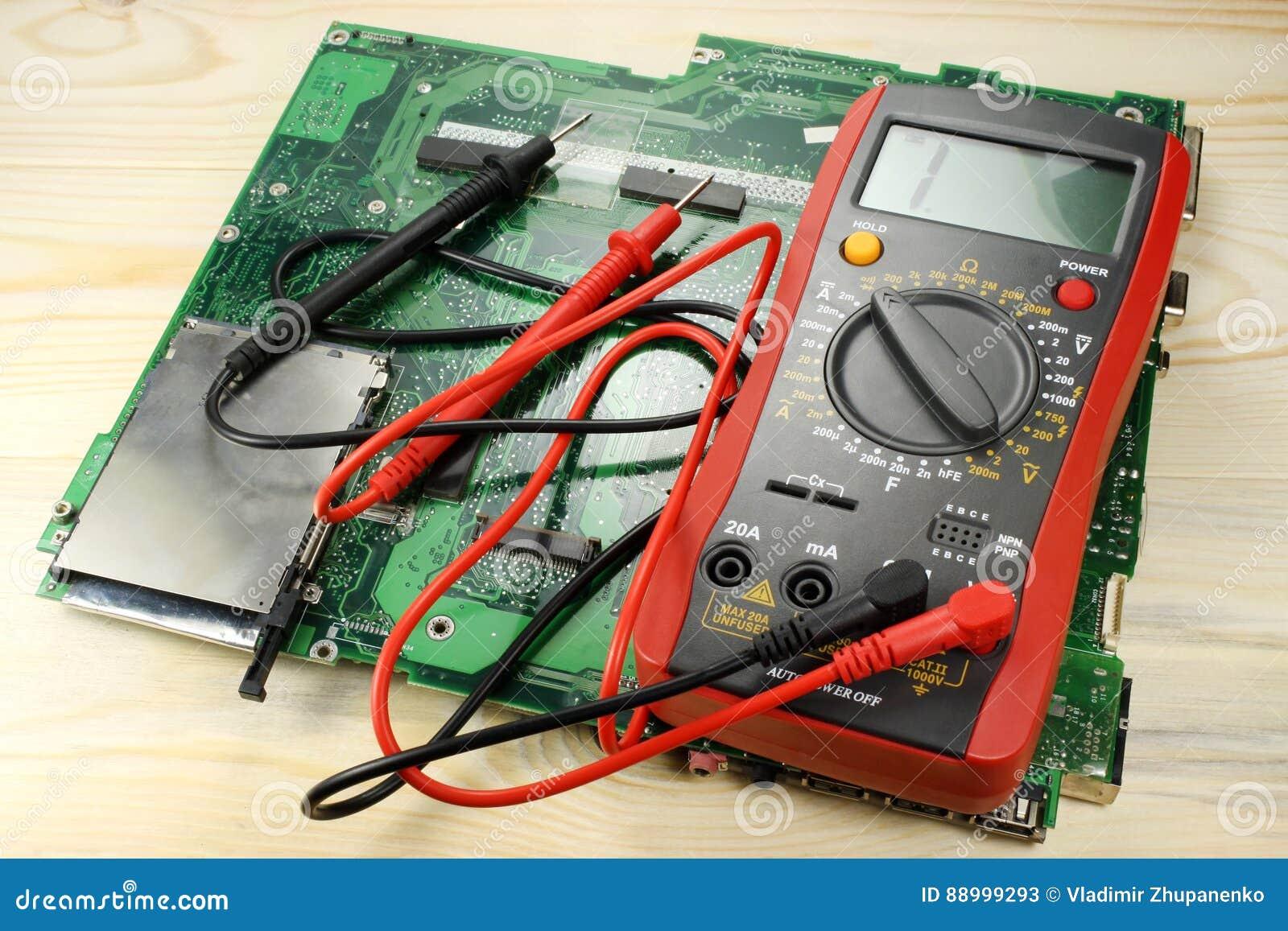 Multimetro di Digital con il circuito su una tavola di legno