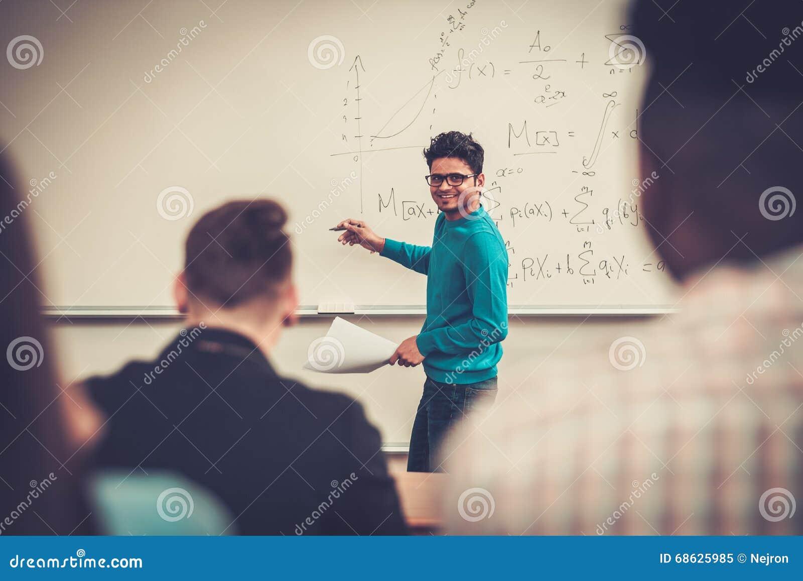 Multinationell grupp av gladlynta studenter som tar en aktiv del i en kurs, medan sitta i en hörsal