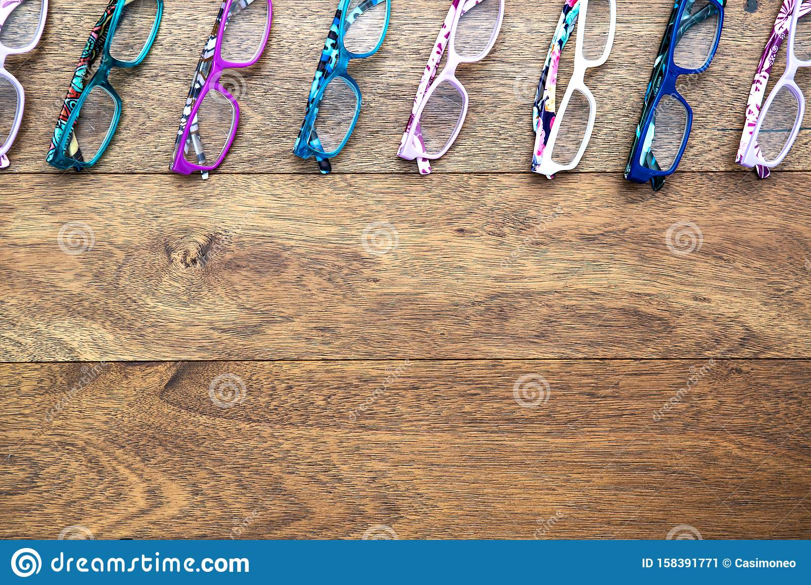 Multiple colored eye glasses lined on wooden deck. Eye Health Concept. Top View with room for text