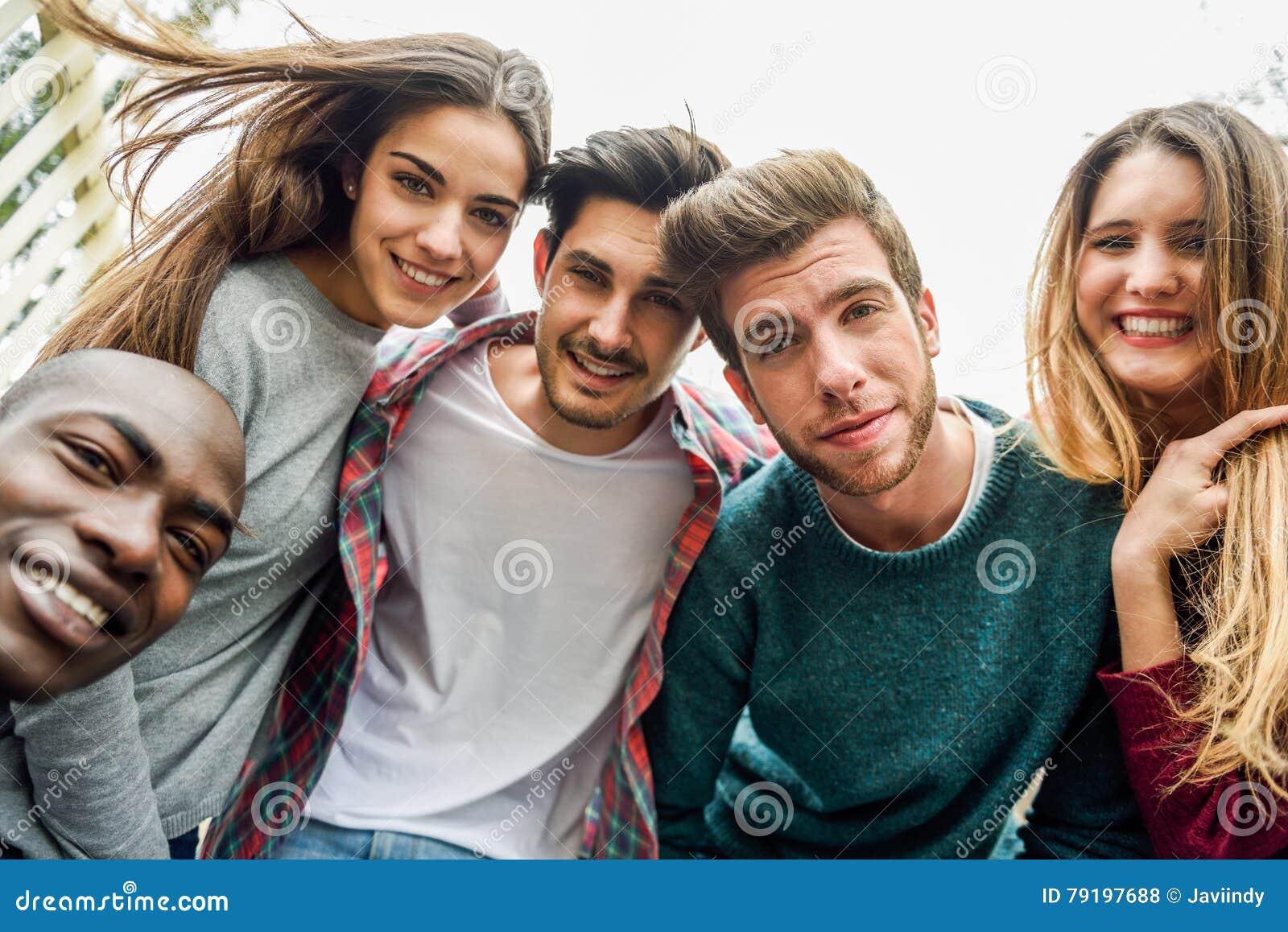 Multiracial группа в составе друзья принимая selfie