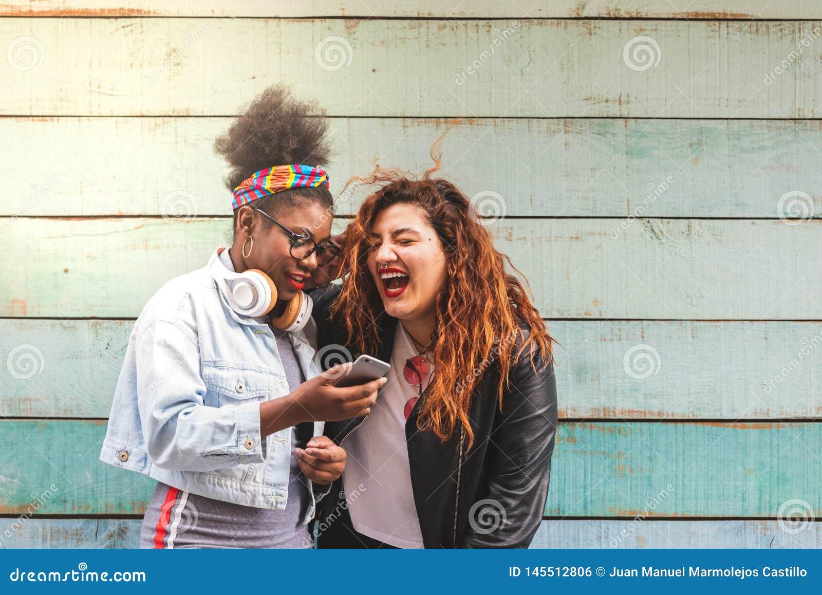 Multiracial девушки подростка используя Outdoors мобильного телефона