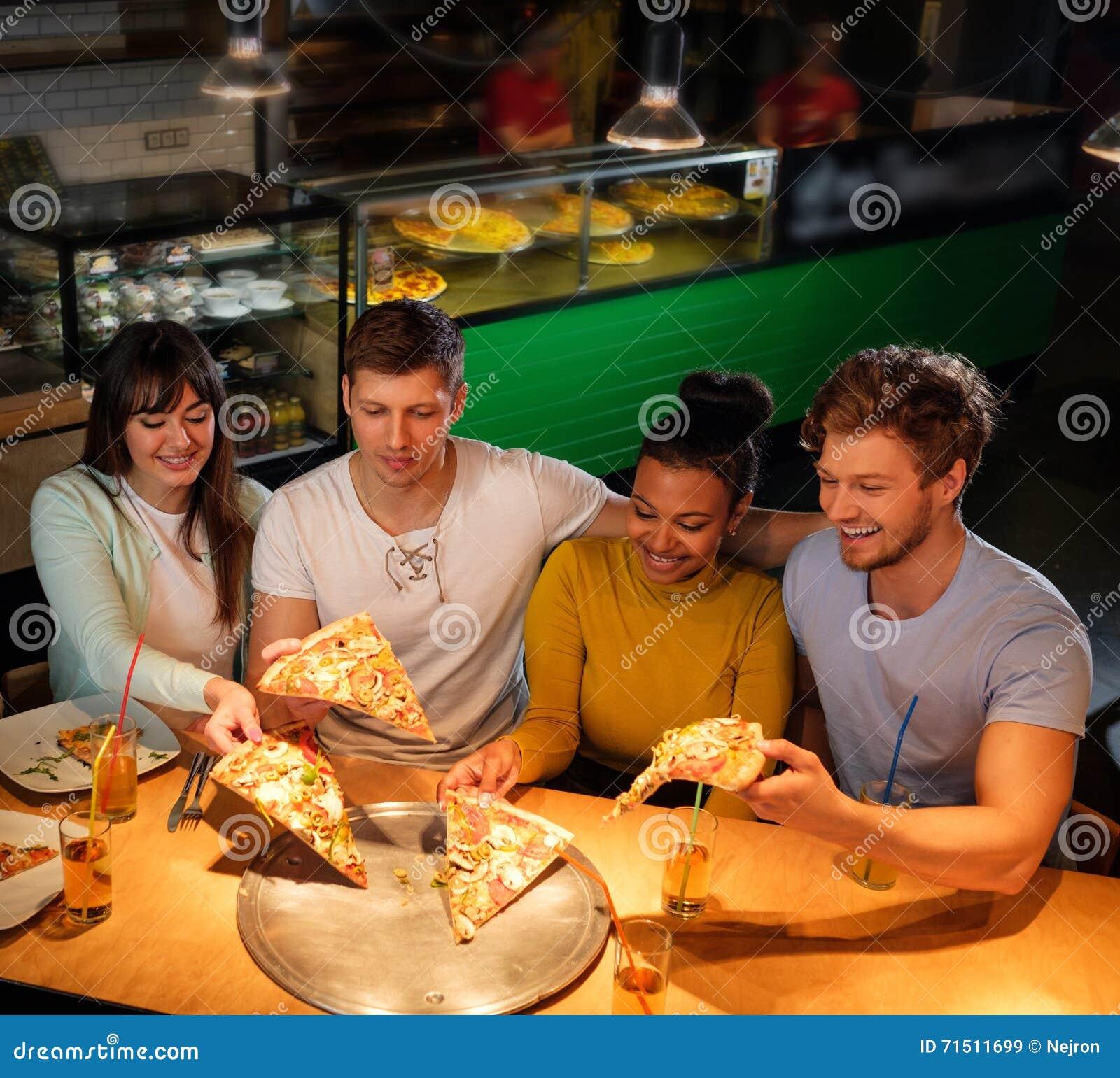 Multiracial друзья имея потеху есть в пиццерии