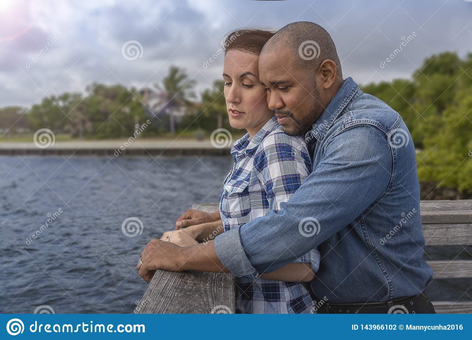 A multiracial couple looks over the pier
