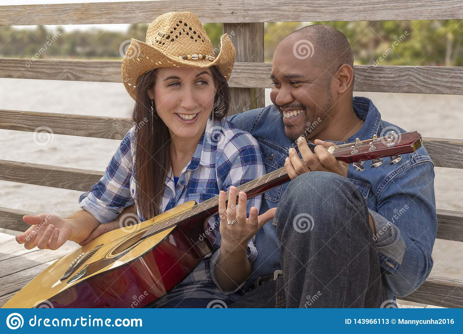 A multiracial couple sits on a deck laughing out loud