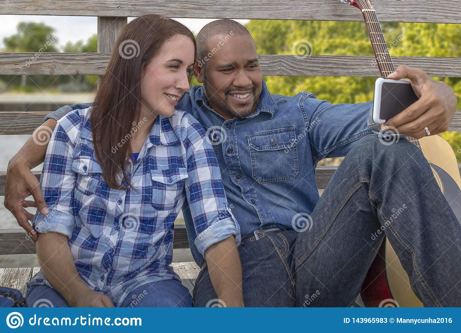 A multiracial couple sits on a deck with smartphone