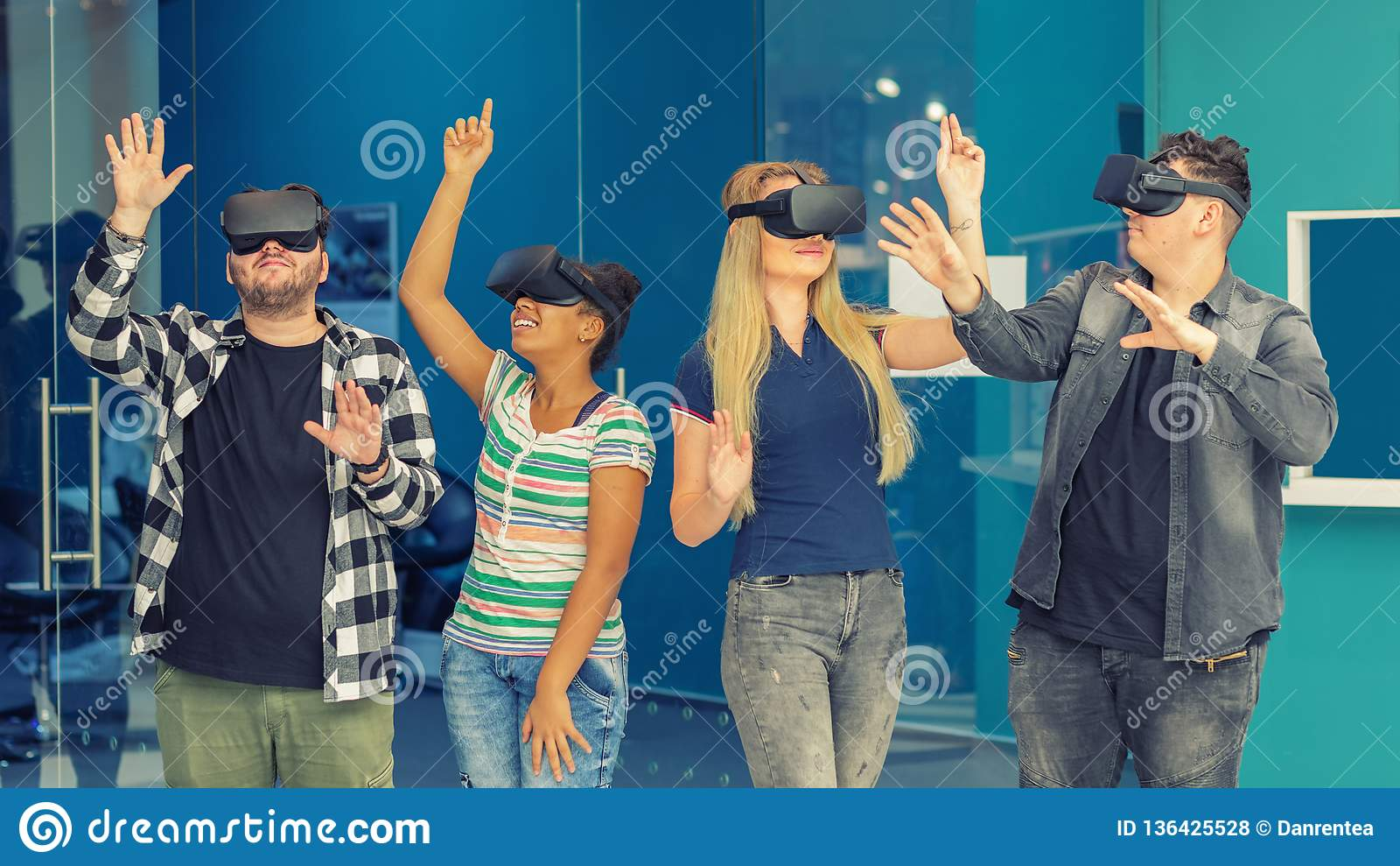 Multiracial friends group playing on vr glasses indoors. Virtual reality concept with young people having fun together.