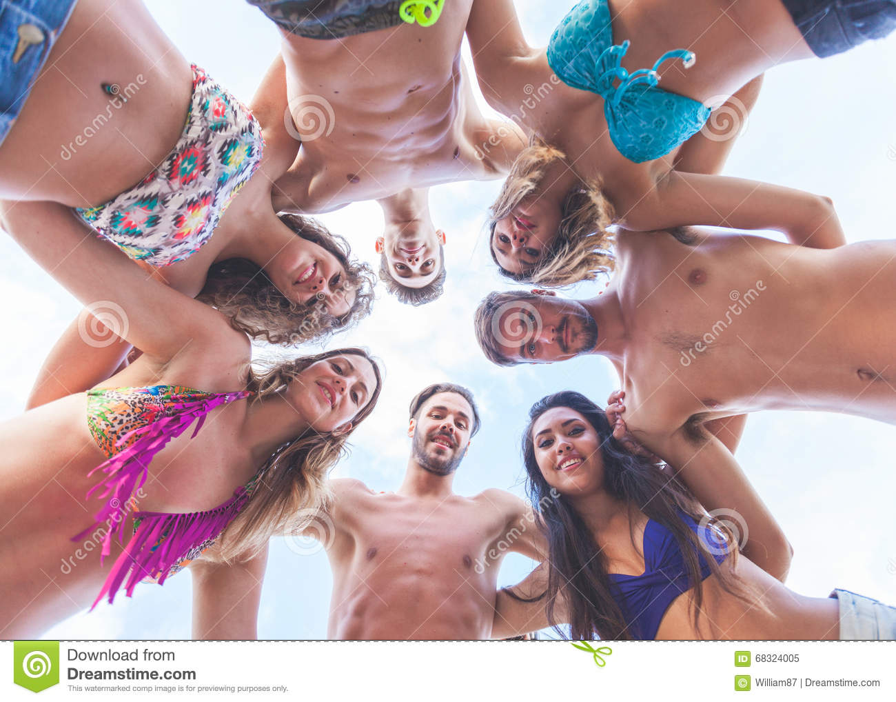 Multiracial group of friends embraced at seaside, bottom view.
