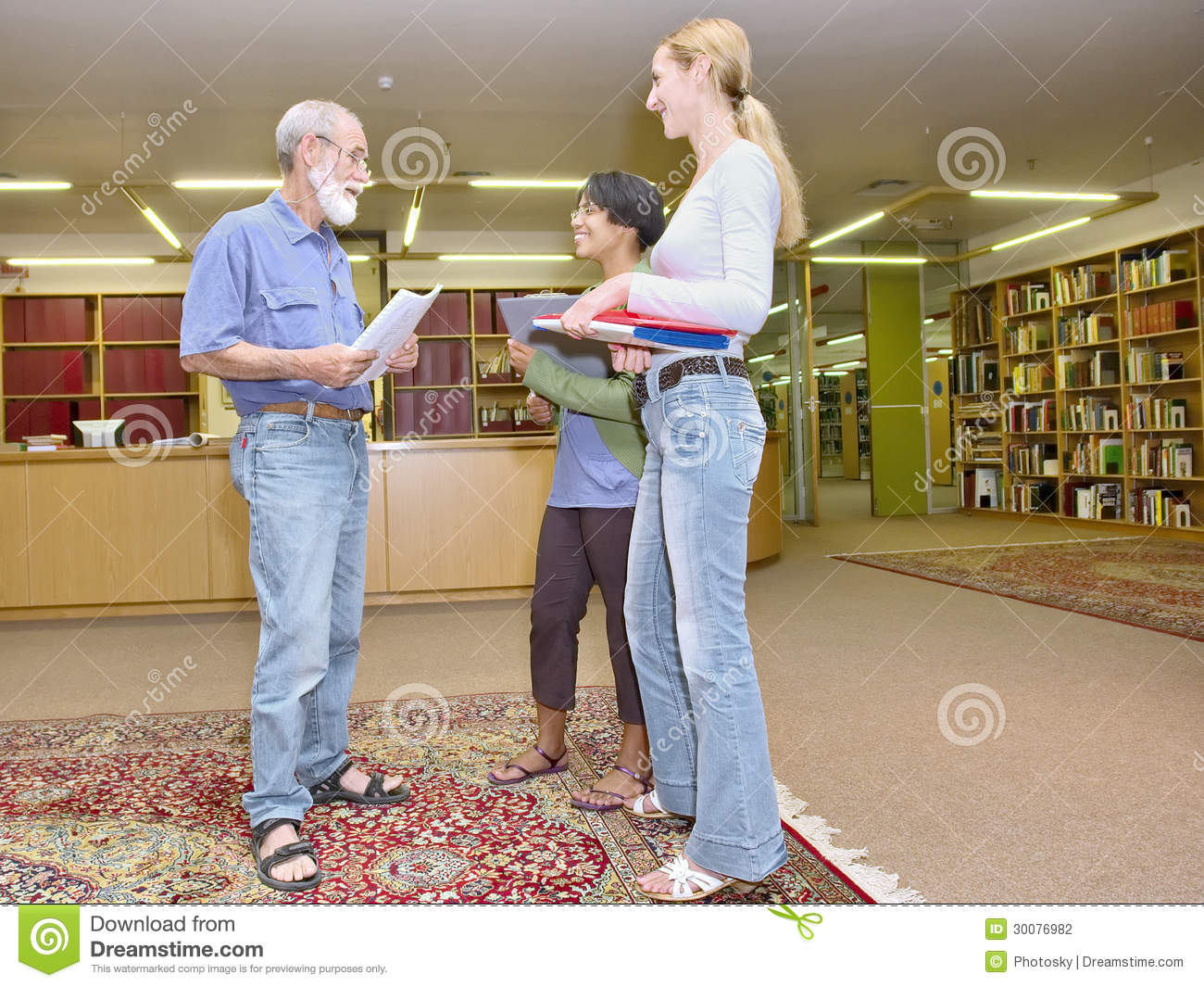 Multiracial group of friendly people chatting in library