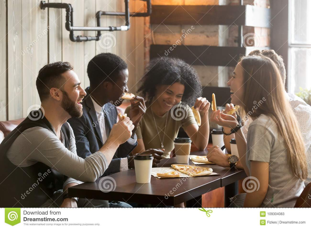 Multiracial happy young people laughing eating pizza together in