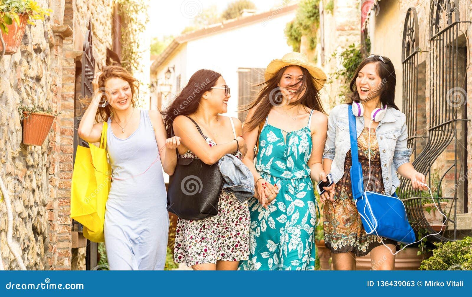 Multiracial millennial dziewczyny chodzi i opowiada w starej grodzkiej wycieczce turysycznej - Szczęśliwe dziewczyny ma zabawę wo