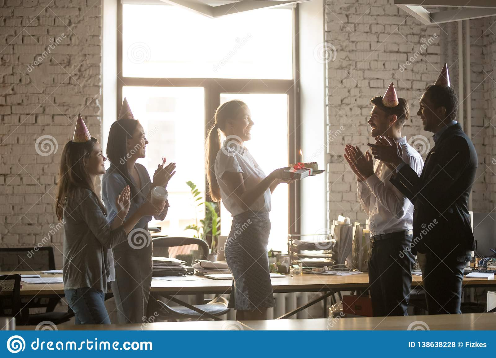 Multiracial Millennial Employees Wear Party Hats Congratulate Colleague With Birthday Present Cake And Gift Excited Diverse Workers Laugh Have Fun