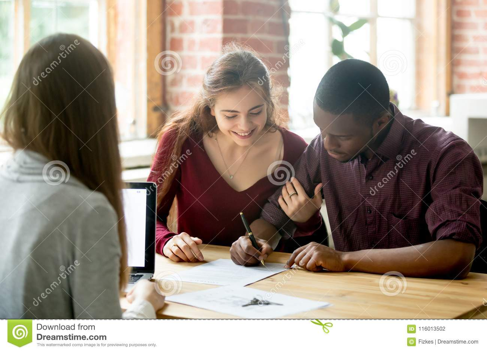 Multiracial pary podpisywania transakcja od agenta nieruchomości