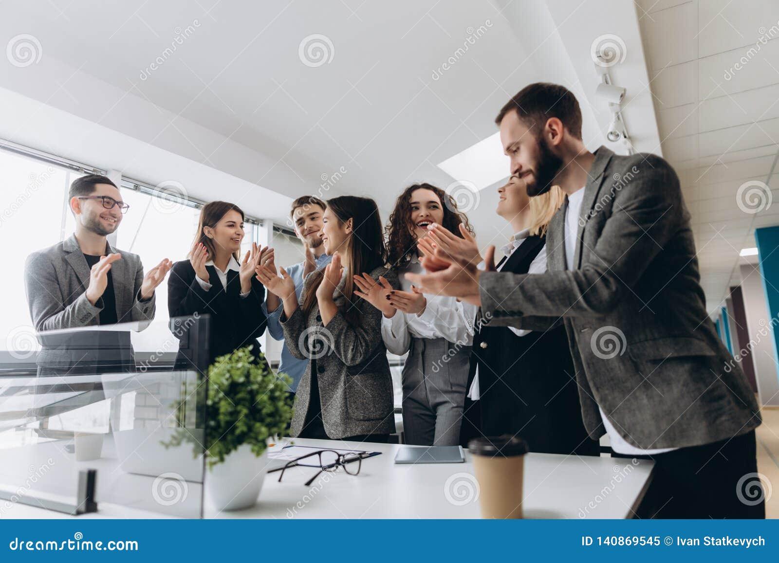 Multiraciale groep bedrijfsmensen die handen slaan om hun werkgever geluk te wensen - Bedrijfteam, staande ovatie na a
