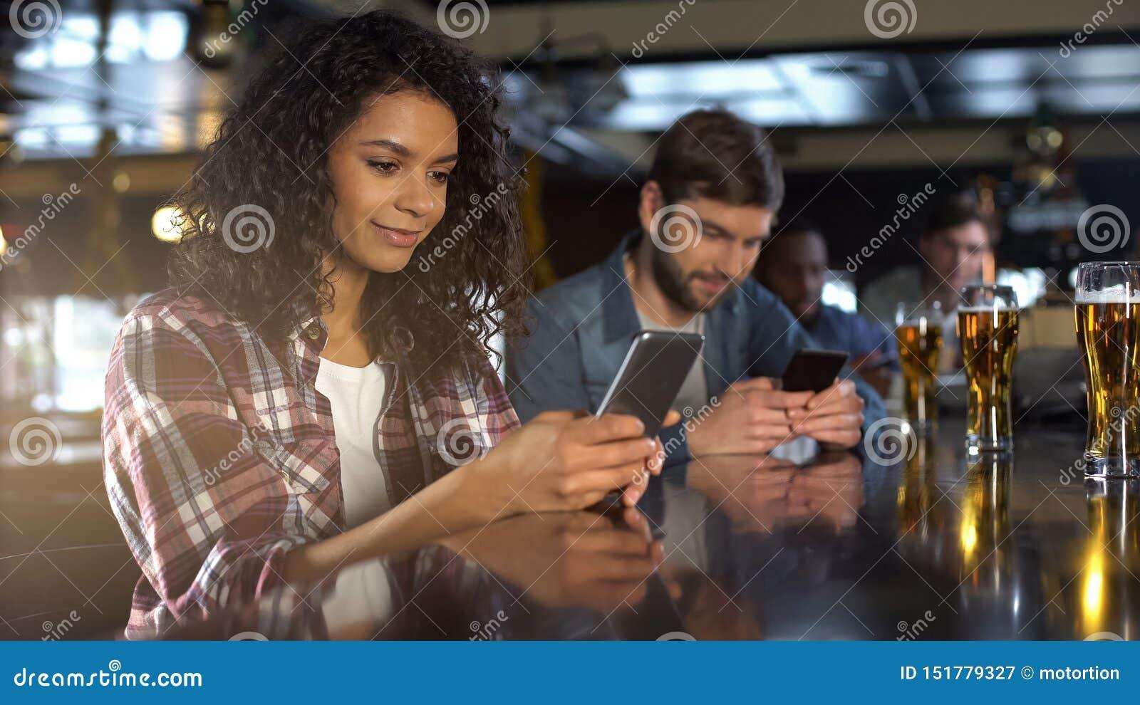 Multiraciale mensen die telefoons in bar in plaats van mededeling, verslaving scrollen