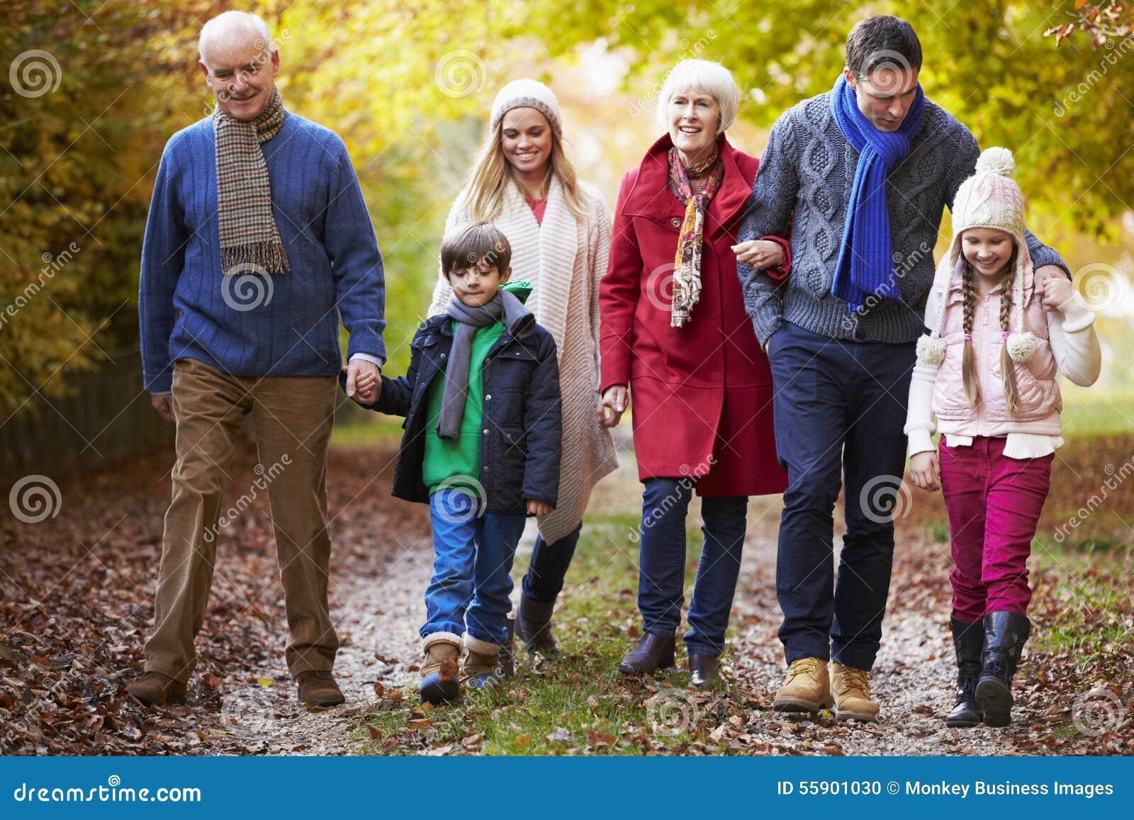 Multl utvecklingsfamilj som promenerar Autumn Path