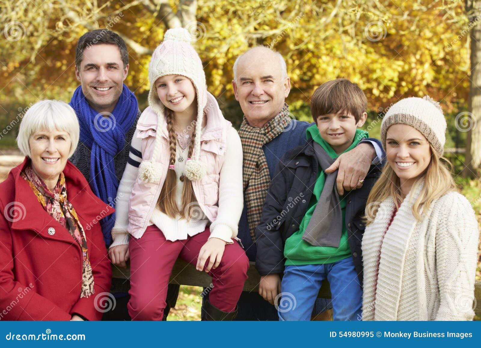 Multl utvecklingsfamilj vid trästaketet On Autumn Walk