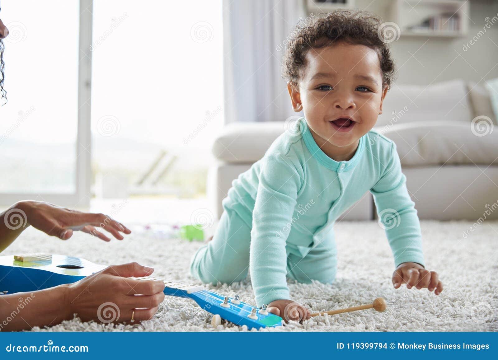 Mum da raça misturada e filho da criança que joga em casa, perto acima