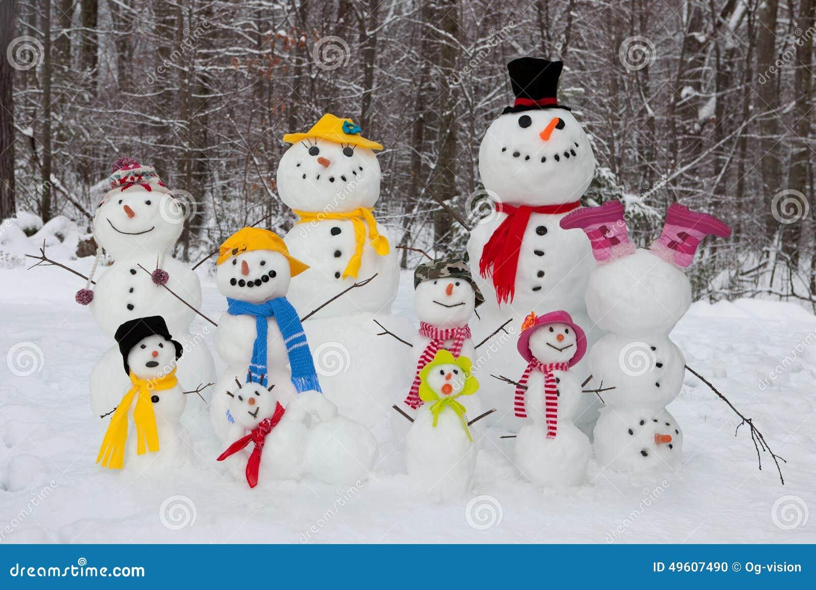 Mum för farsafallsfamilj som ler utomhus vinter för snowsnowmanson