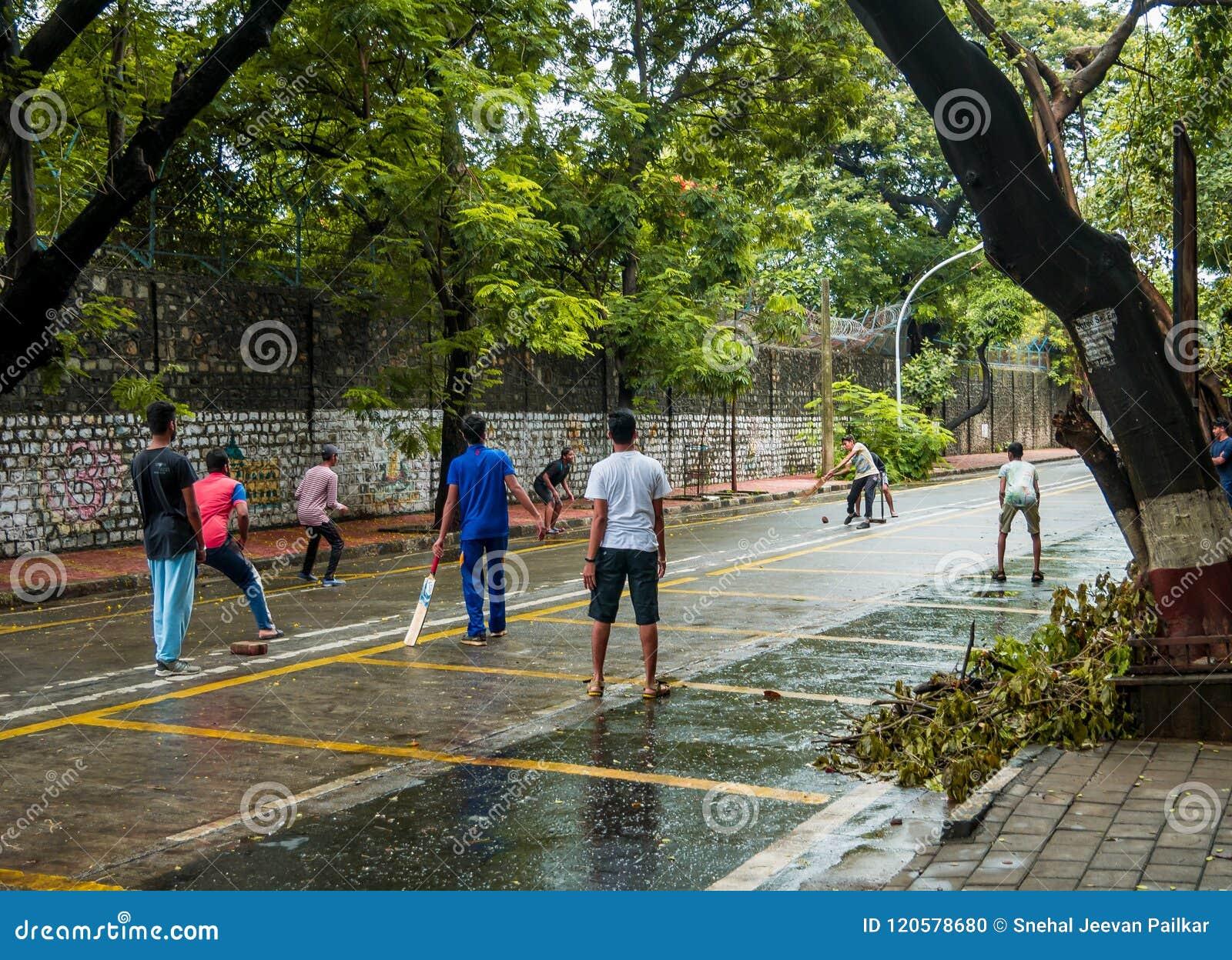 boys playing cricket on streets at ballard estate, south mumbai