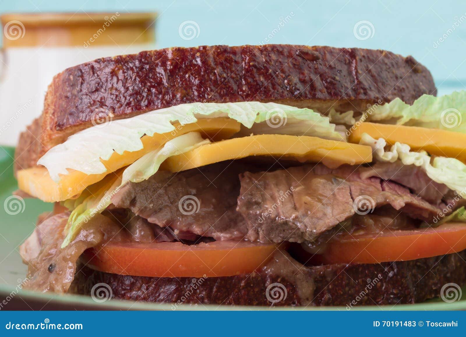 Mun som bevattnar steknötkött och skysmörgåsen