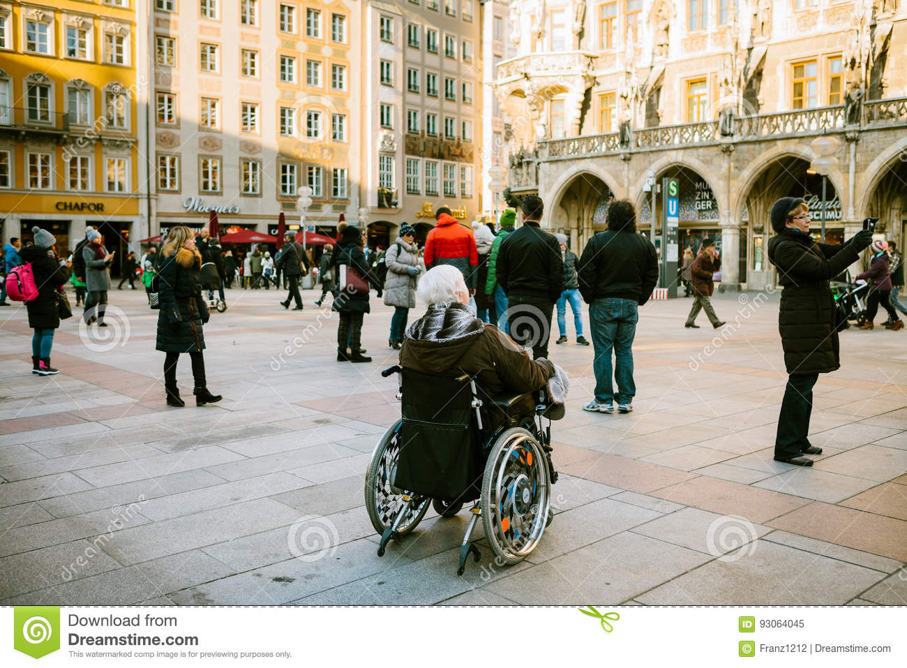 Munich, Germany, December 29, 2016: An elderly woman in a wheelchair examines the sights of Munich on the main square of