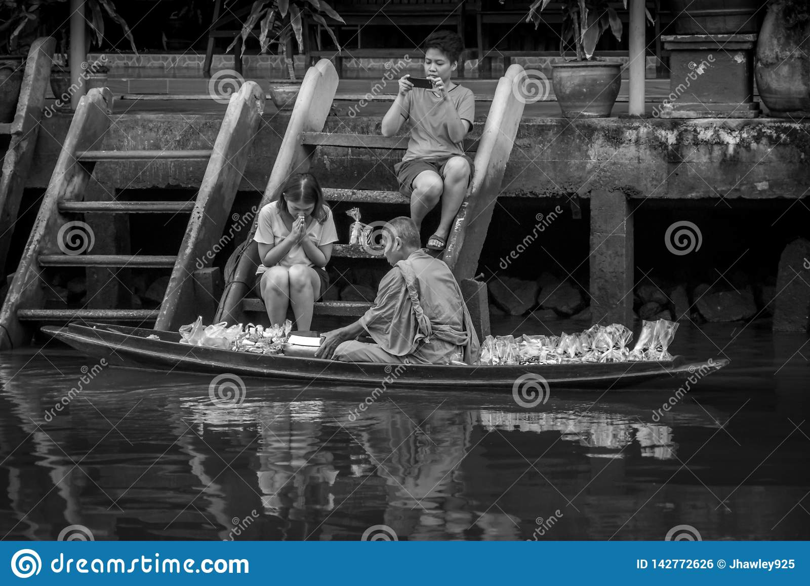 Munk Collecting Alms på den Amphawa floden