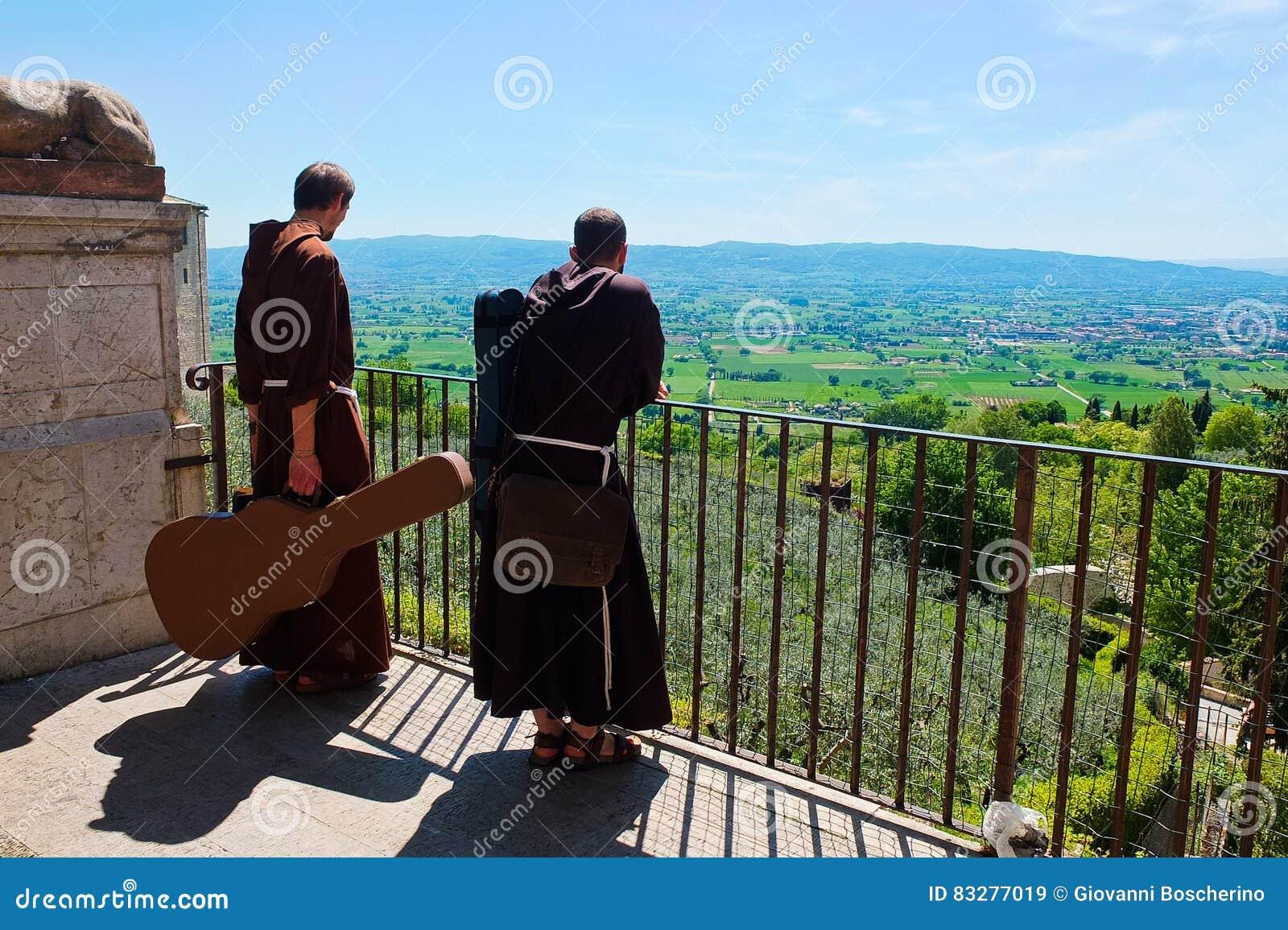 Munkar med gitarren i staden av Assisi