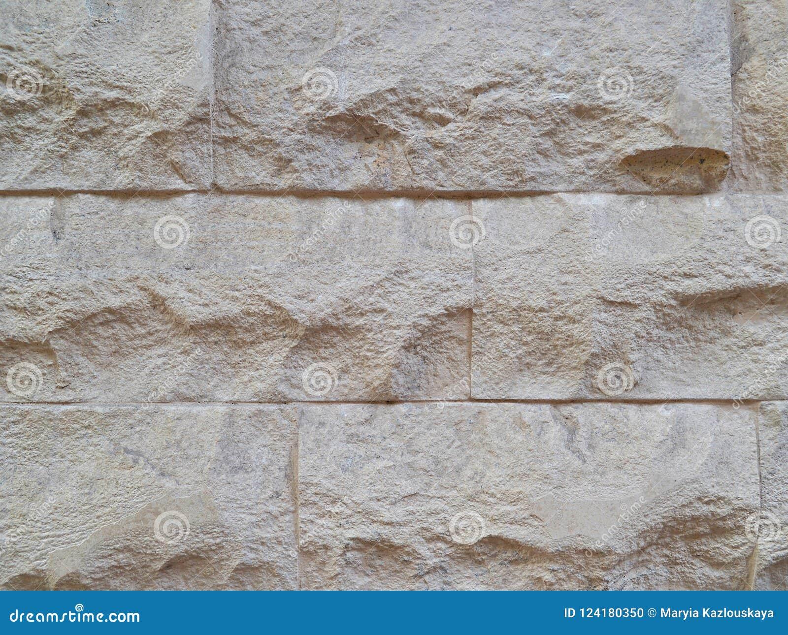 Mur décoratif, construit des dalles en pierre taillées de couleur beige