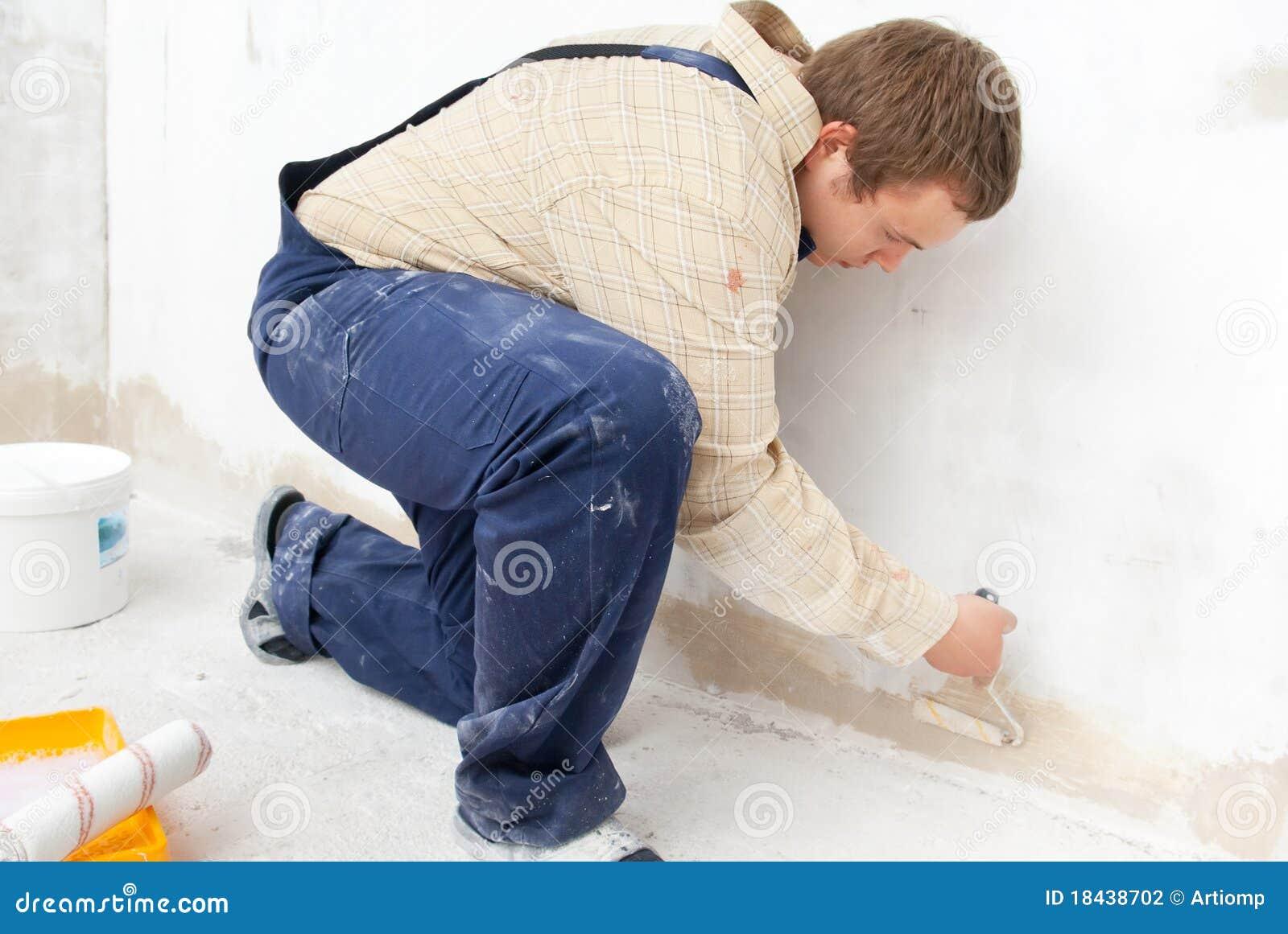 Mur de peinture d homme avec le petit rouleau